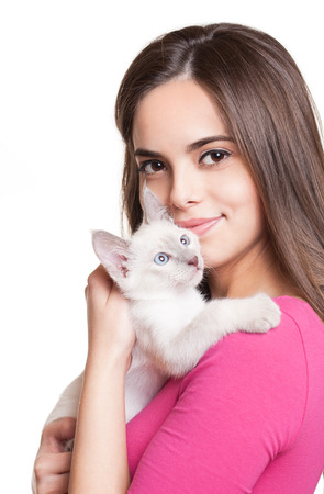 Gorgeous young brunette holding sweet young siamese kitten.