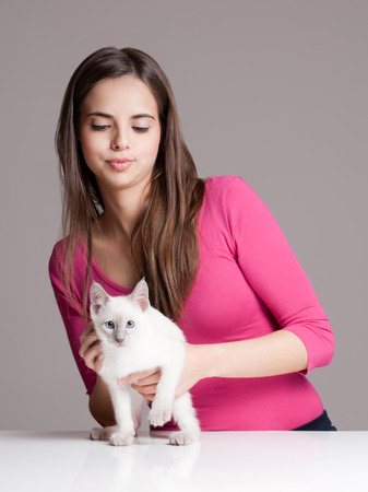 Gorgeous young brunette holding sweet young siamese kitten. photo