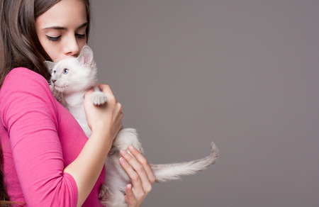 Portrait of a beautiful brunette holding a cute kitten. Standard-Bild