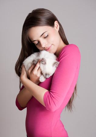 Prachtige jonge brunette die lieve jonge siamese kitten.
