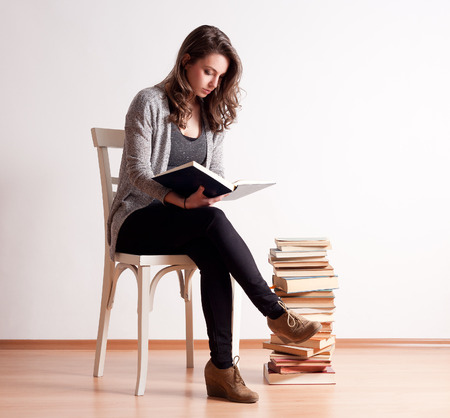girl reading book: Gorgeous young brunette student woman next to column of books.
