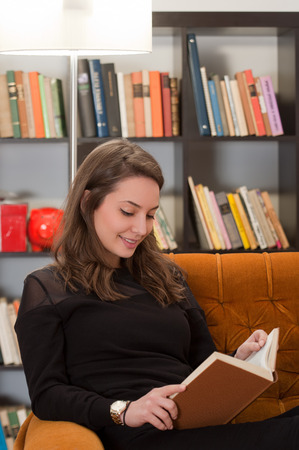 Portrait of a beautiful young brunette woman reading a book. photo