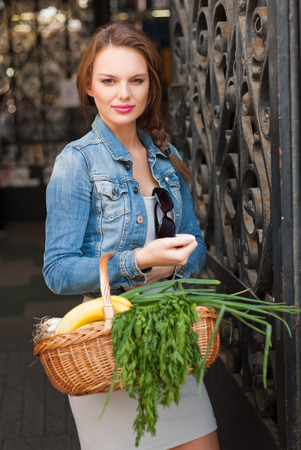 Beautiful young brunette woman on a market getting fresh food. photo