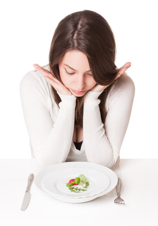 portions: Portrait of a frustrated looking young brunette woman with plate of vegetables. Stock Photo