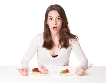 awe: Portrait of a beautiful young brunette woman in diet dilemma.