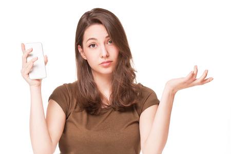 dudas: Retrato de una joven morena dulce usando el teléfono móvil.