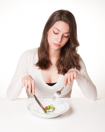 dilemma: Portrait of a frustrated looking young brunette woman with plate of vegetables. Stock Photo