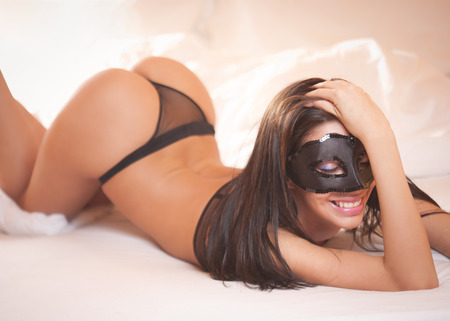 Sensual lavish brunette beauty wearing black lingerie in bed.