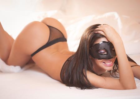 erotico: Sensual sontuosa bellezza bruna indossare lingerie nera a letto.