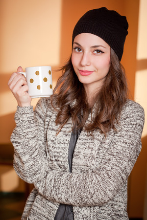 Portrait of a gorgeous young brunette woman relaxing with mug of hot beverage. Banco de Imagens