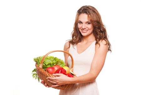 isolated white background: Beautiful young brunette woman posing with basket of fresh vegetables.