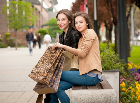 Two gorgeous young brunettes holding shopping bags. photo