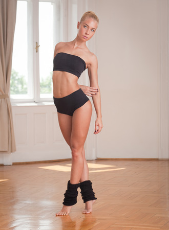 black bra: Gorgeous fit young blond woman practicing dance moves.