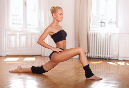 dynamic movement: Young blond fitness beauty doing dance moves. Stock Photo