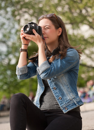 looking away from camera: Beautiful happy young brunette taking photographs.