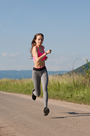 running pants: Fit and agile young brunette woman running outdoors in the sunshine. Stock Photo