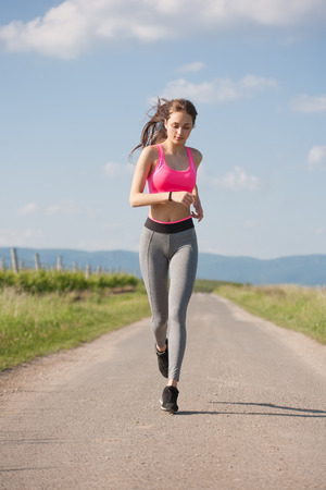 running pants: Young brunette woman running outdoors in sunny nature.
