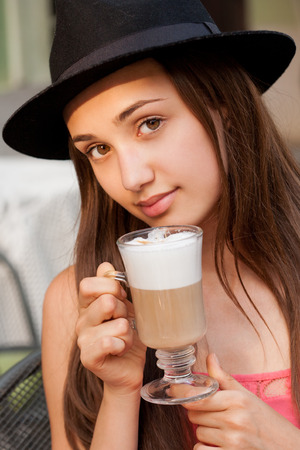 women coffee: Portrait of a beautiful young brunette woman sitting outdoors in coffee shop.