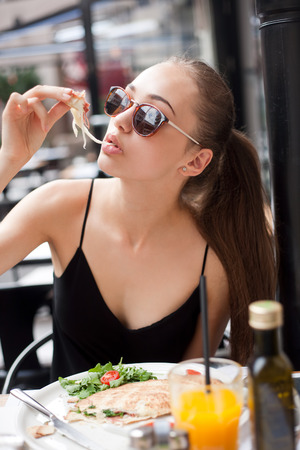 restaurante italiano: Mujer morena joven divirtiéndose comida en el restaurante italiano.