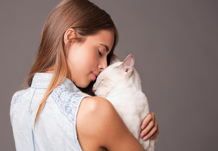 hispanic girl: Portrait of a brunette beauty with siamese cat.