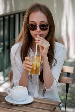 a straw: Stylish young brunette beauty having tasty refreshments in street coffee shop. Stock Photo