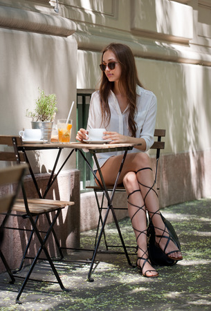 refreshments: Stylish young brunette beauty having tasty refreshments in street coffee shop. Stock Photo