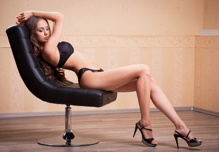 nude girl sitting: Portrait of a beautiful slim brunette woman in lingerie.