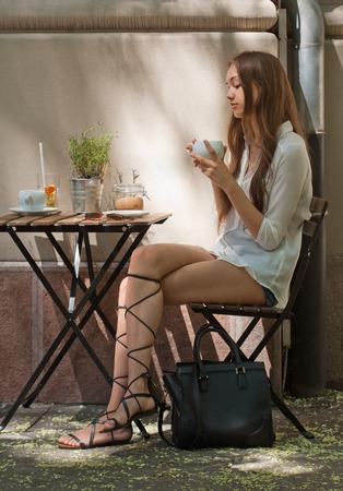 femme brune sexy: Élégant jeune beauté brune ayant des rafraîchissements savoureux dans la rue café. Banque d'images