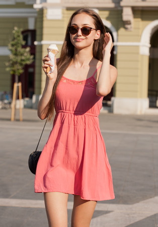 Refreshments: Beautiful young brunette woman having ice cream refreshment in summer sunshine. Stock Photo