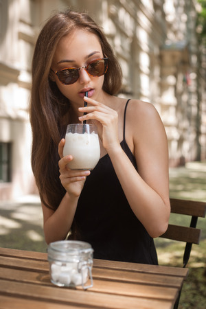 refreshment: Gorgeous young brunette woman having ice coffee refreshment.