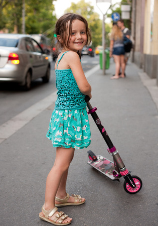 Cute young girl riding her scooter on city streets.