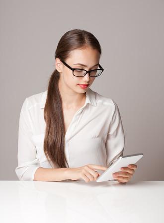 women smiling: Portrait of a gorgeous brunette woman using tablet computer. Stock Photo