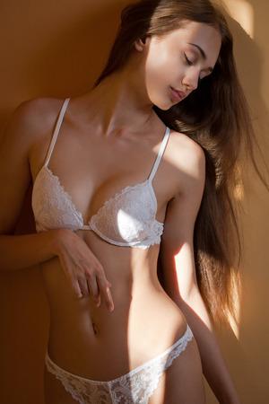 sexy nude women: Artistic portrait of brunette lingerie beauty in creative lighting. Stock Photo