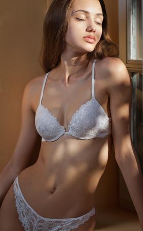 desnudo artistico: Retrato artístico de sensual morena lencería en la iluminación creativa. Foto de archivo