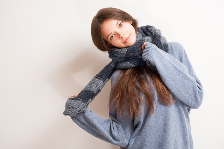 fall winter: Cold weather coming, cute brunette girl in scarf and sweater. Stock Photo