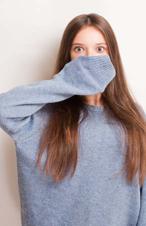 get ready: Get ready for the cold, brunette girl in large blue sweater. Archivio Fotografico