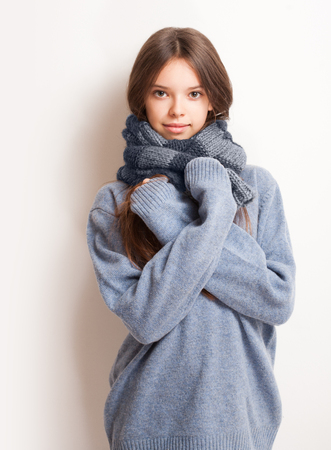 sweater girl: Cold weather coming, cute brunette girl in scarf and sweater. Stock Photo
