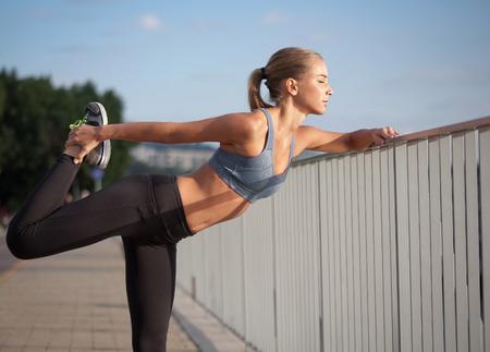 stretching: Hermosa joven de la aptitud ajuste mujer rubia urbano.