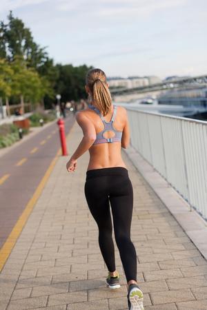 gente corriendo: Atlético belleza rubia haciendo rutina de ejercicios en la tarde en la ciudad. Foto de archivo