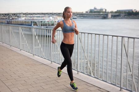 personas corriendo: Hermosa joven de la aptitud ajuste mujer rubia urbano.