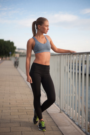 running pants: Beautiful athletic blond womans late afternoon workout in urban setting. Stock Photo