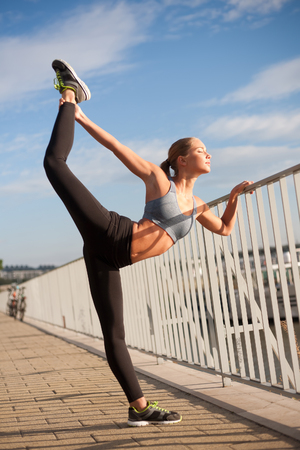 running pants: Athletic blond beauty doing fitness routine in at evening in the city.