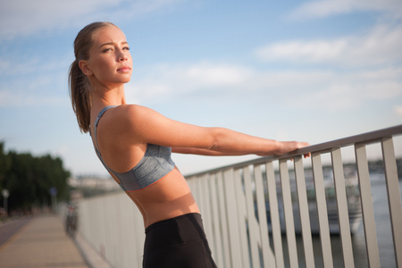 running pants: Fit lean blond beauty exercising outdoors in the city.