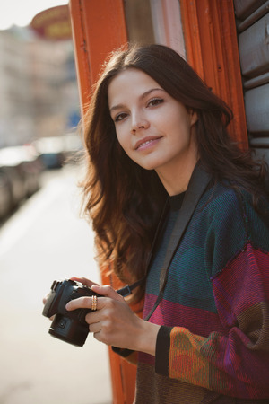 PRETTY WOMEN: Young brunette woman with ther camera on the streets.