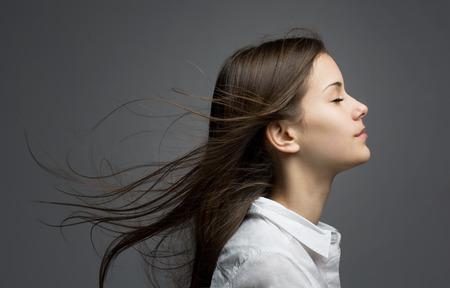 soñando: Retrato de una joven belleza morena de ensueño con el pelo azotado por el viento.