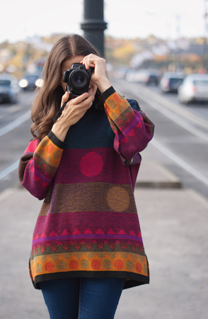 camera girl: Young brunette woman with ther camera on the streets.