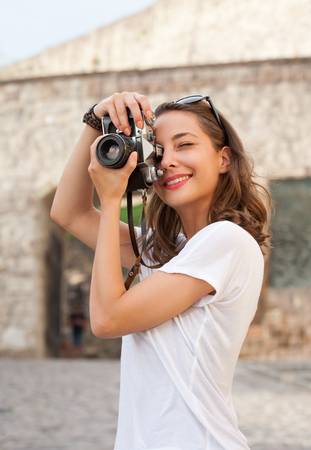 camera girl: Portrait of a young brunette tourist woman taking photo.