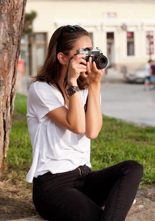 analog camera: Gorgeous young brunette woman using analog camera. Stock Photo