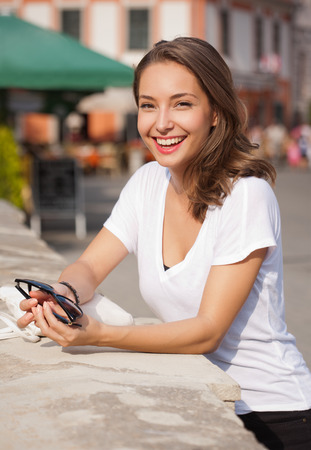 brunette girl: Portrait of a young brunette tourist woman taking photos.