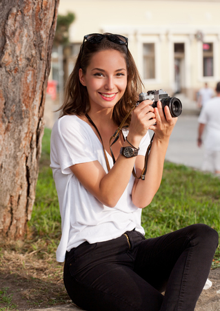 gorgeous girl: Gorgeous young brunette woman using analog camera. Stock Photo